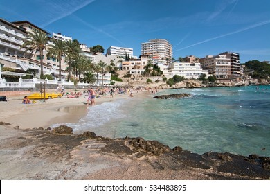 CALA MAYOR, BALEARIC ISLANDS, SPAIN - OCTOBER 23, 2016: People on the beach in bathing suits on a sunny day on October 23, 2016 in Cala Mayor, Balearic islands, Spain.
