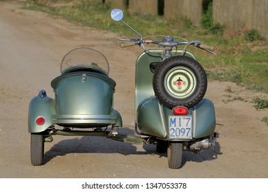 Calabria, Italy - Giugna, 03, 2009: Piaggio Vespa sidecar on a dirt road, an ancient Italian motorcycle