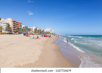 Calafell, Spain - August 13, 2014: People relax on beach of Calafell resort town in sunny summer day. Tarragona region, Catalonia, Spain