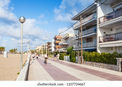 Calafell, Spain - August 18, 2014: People walk on main coastal street of Calafell town in sunny summer day. Tarragona region, Catalonia, Spain