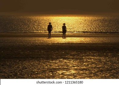 CALAIS, FRANCE, JULY 26, 2018, Silhouettes of couple walking on the north sea beach with reflection of the setting sun in the water and sand , Calais, 26 Jul 2018