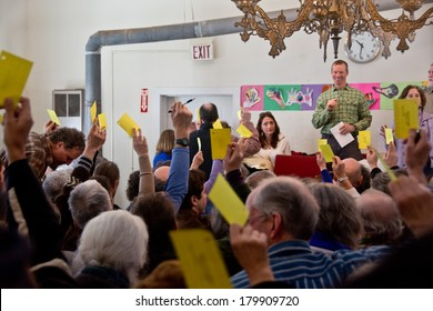 Calais, Vermont, USA - March 4, 2014: Voters raise yellow cards to register their vote on this vote from the floor at the Calais Town Hall during the school board meeting on Town Meeting Day.