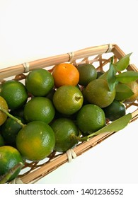 Calamansi fruit on small woven basket isolated on white