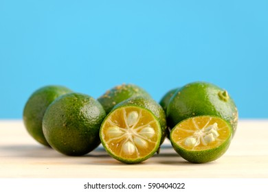 Calamansi on wooden table and blue background