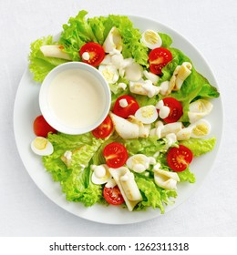 calamari salad with lettuce, tomatoes, and quile eggs dressed with mayonnaise based sauce