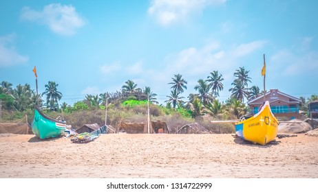 Calangute, Goa / India - 04 22 2017: Typical fisherman boats on Calangute beach in the north Goa. Foumous touristic spot for summer holidays near Candolim and Anjuna in India with coconut palms.