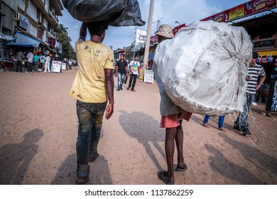 Calangute, Goa, India - January 19, 2017: Two poor Indians collected garbage in packages and go to take it for money.