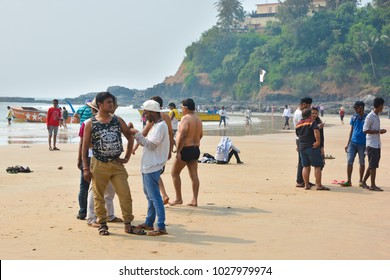 CALANGUTE, INDIA - NOVEMBER 16, 2017 : Indian tourists walk and sunbathe on the beach in North Goa