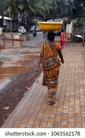 CALANGUTE, INDIA - SEP 18, 2017 - Woman in orange sari on flooded street  after monsoon shower, Calangute, Goa, India