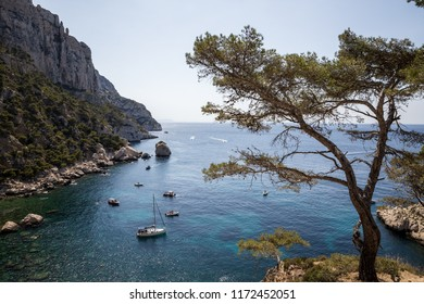CALANQUES DE MARSEILLE, FRANCE - JUNE 18, 2018: boats in calm harbour and beautiful rocky mountains in Calanques de Marseille (Massif des Calanques)