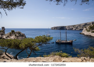 CALANQUES DE MARSEILLE, FRANCE - JUNE 18, 2018: boats in calm harbour and beautiful cliffs in Calanques de Marseille (Massif des Calanques), france