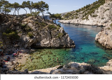 CALANQUES DE MARSEILLE, FRANCE - JUNE 18, 2018: people resting on beach and beautiful landscape with rocky mountains and calm harbour, Calanques de Marseille (Massif des Calanques)