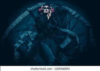 Calavera Catrina sitting on a throne. Sugar skull makeup. Dia de los muertos. Day of The Dead. Halloween.