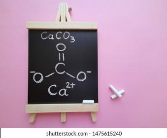 Calcium carbonate is a chemical compound with the formula CaCO3. Structural chemical formula of CaCO3 molecule on a black chalkboard with drawing chalks. Chalk is a form of calcium carbonate.