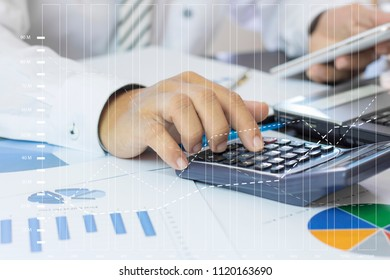 Calculate budget and business planning concept, two people counting revenue and expenditure by using calculator and looking at phone and paper graph on desk in home office