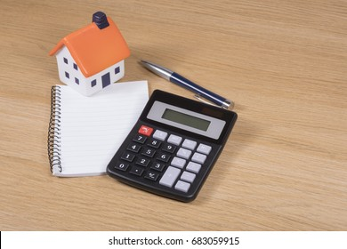 Calculating the costs of home improvements or purchase in a conceptual image with a model toy house, calculator, notebook and pen on a wooden table