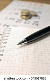 Calculating Expenses concept. Pen, calendar, notebook, and coins