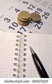Calculating Expenses concept. Pen, calendar, notebook, and coins.