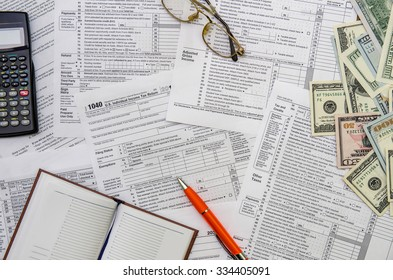 Calculating income tax return with money and pen