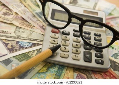 Calculating numbers for income tax return with glasses pen and calculator.  notes and bills of different states. international banknotes. wooden pen on various money bill