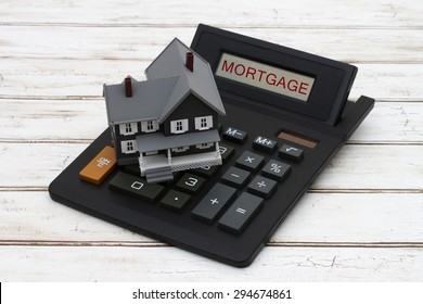 Calculating your mortgage payments, A gray model house on a calculator with word Mortgage over a distressed wood background