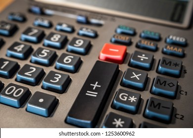 Calculator adding machine keyboard with tight focus on addition, subtraction and numeric keys. Numerical keyboard with gray and orange plastic calculation buttons.