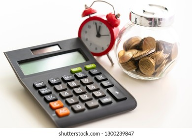 Calculator, alarm watch and coins jar. Selective focus. Terms of tax payments concept.