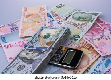 Calculator, American dollar banknotes and Turksh Lira banknotes side by side on white background