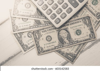 Calculator with american dollars on the wooden table background, finance concept
