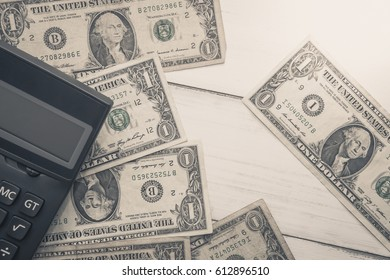 Calculator with american dollars on the wooden table background, finance concept, pencil, phone
