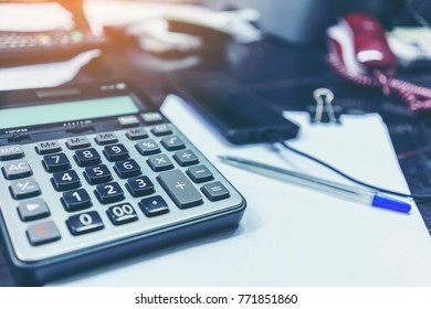 Calculator and ball pen on the table in the office