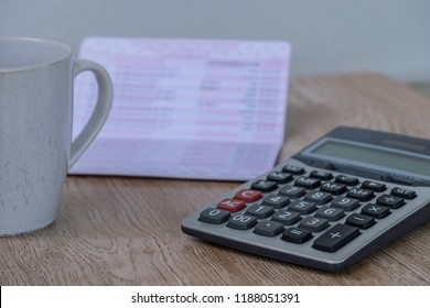 calculator, bankbook ,coffee cup  Put on a wooden table.