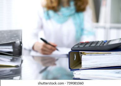 Calculator and binders with papers are waiting to be processed by businesswoman or secretary back in blur. Internal Audit and tax concept