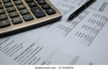 Calculator and black pen with accounting report and financial statement on desk. Accounting business concept.
