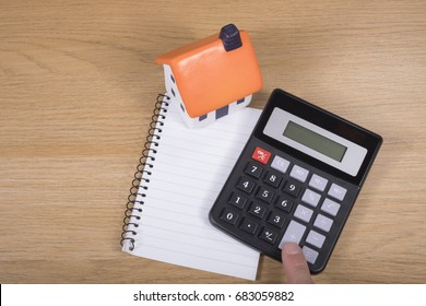 Calculator with blank notepad and model house on a wooden desk with a male finger punching the keys for an answer in calculating costs viewed from above