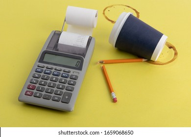 a calculator broken pencil and a cup of coffee tipped over in frustration at tax time