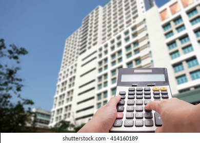 The calculator and building under construction in background , construction cost concept