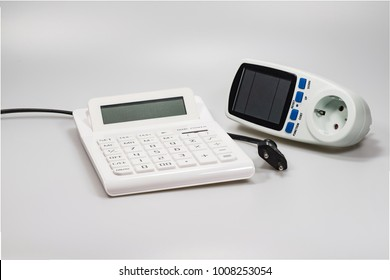 A calculator, cable, plug and a consumption meter on a white background