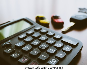 the calculator and car model with keys of a car background on desk, business finance concept