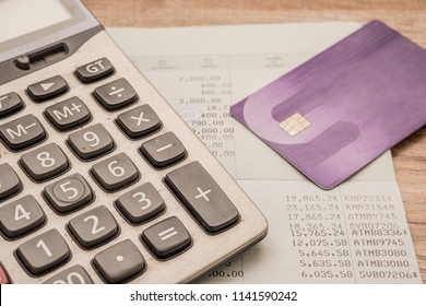 Calculator, cash card, bankbook Put on a wooden table.