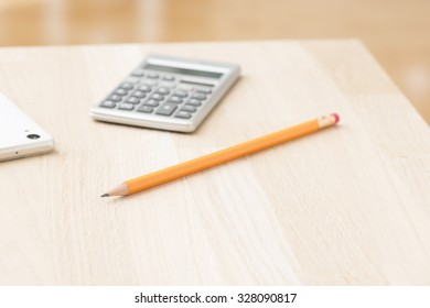 Calculator cell phone and pencil on office desk. Concept of financial work and business project report.