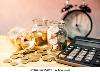 Calculator with coin in currency glass jar and clock on wooden table. Compound interest rate calculation. Financial business plan. Time investment. Saving money concept