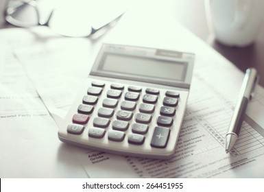 Calculator device on papers with eyeglasses and pen