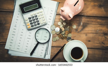 calculator and document with piggy bank on table