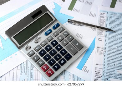 Calculator with documents and pen on table. Tax concept