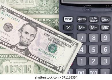 calculator and dollars bills.