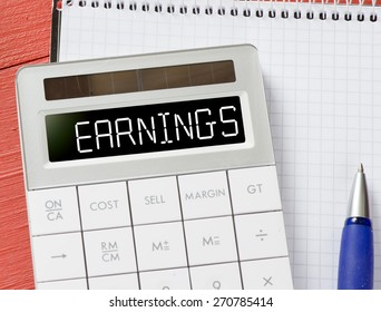 Calculator with earnings word. Calculator with earnings word and notepad, pen on background