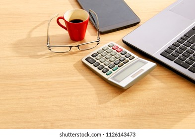 Calculator and eyeglasses with red cup coffee and tablet on wood table backgrounds