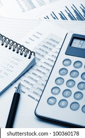 The calculator and the financial report blue toned. A workplace of the businessman
