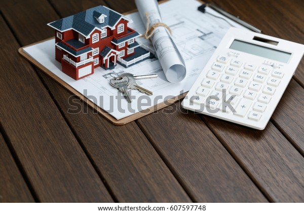 a calculator in front of a Villa house model with a blueprint